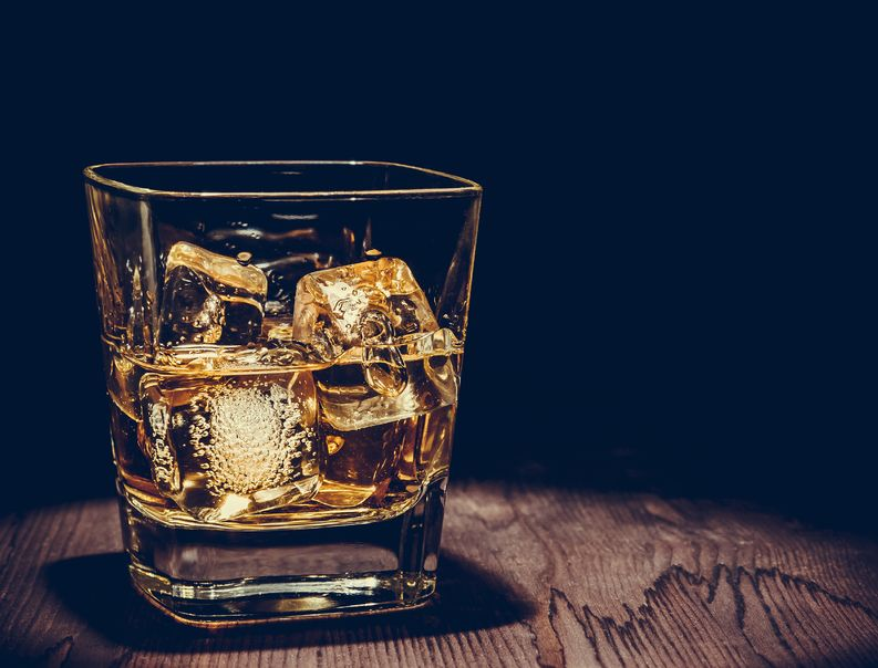 46673642 - glass of whiskey with ice cubes on wood table, warm atmosphere, time of relax with whisky with space for text