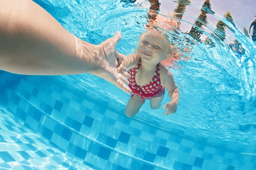 41900312 - joyful baby girl diving underwater with fun and holding parents hand for assistance in swimming pool. healthy active family lifestyle, children water sport activity with mother on summer vacation