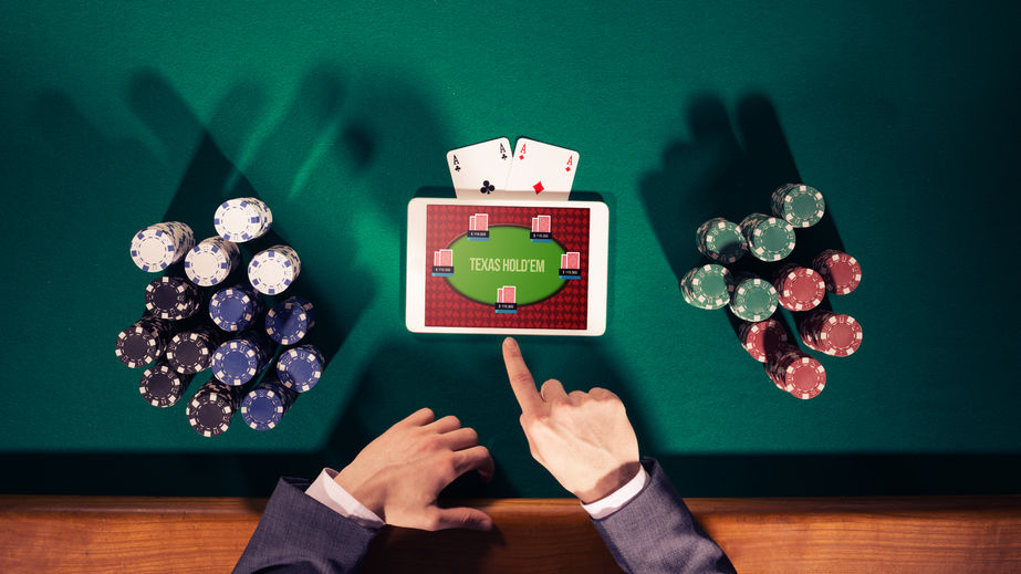 43569275 - poker player's hands with digital tablet, stacks of chips and cards on green table, top view