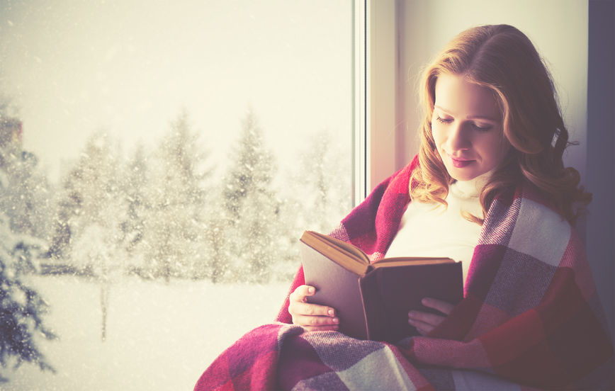48969141 - happy girl reading a book by the window in the winter