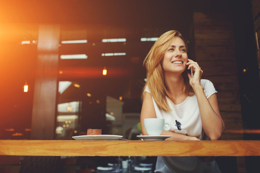 59097698 - young charming woman calling with cell telephone while sitting alone in coffee shop during free time, attractive female with cute smile having talking conversation with mobile phone while rest in cafe