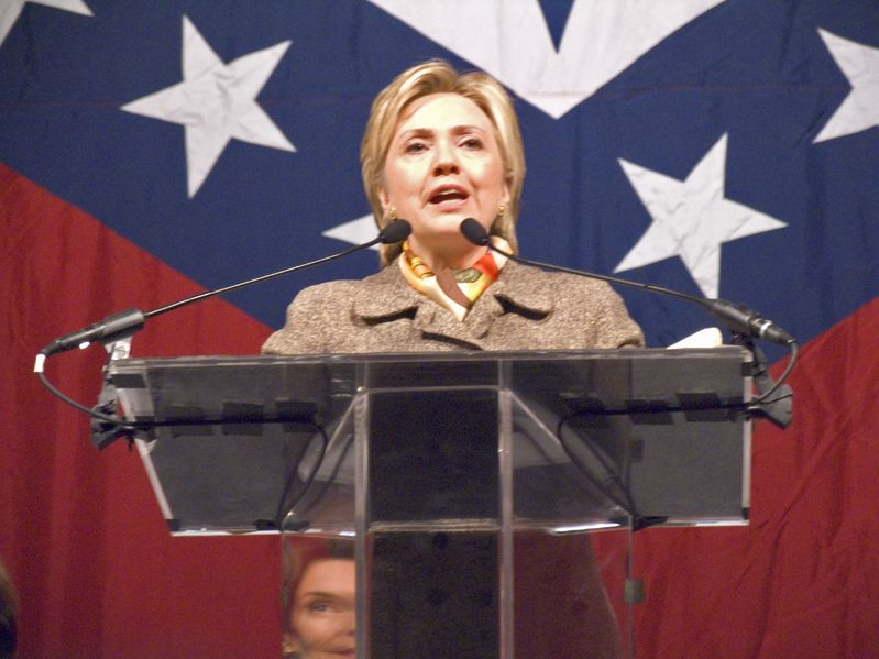 20712139 - sen. hillary clinton (d-ny), wife of former u. s. former president bill clinton, speaks at a little rock, ak luncheon honoring the first ladies of the state in front of the state flag november 17, 2004 in little rock, ak