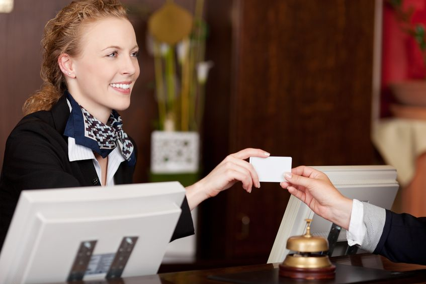 21375244 - smiling stylish beautiful receptionist handing over a blank white card to a client at the reception desk