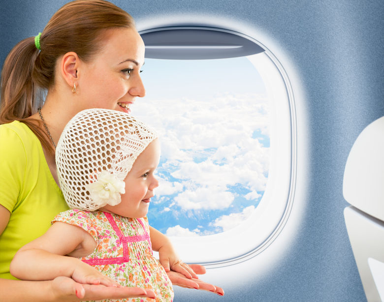 31238755 - happy mother and kid travelling together in airoplane cabin near window