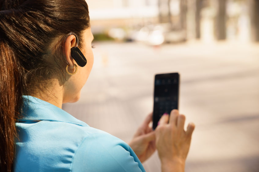34056769 - mid adult hispanic person with mobile phone and bluetooth headset, typing on telephone in the street