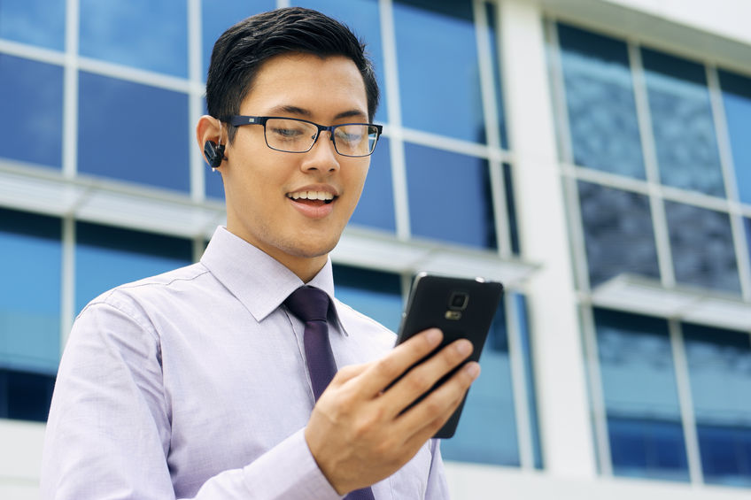 41605842 - young chinese businessman doing video conference call on smartphone and talking with bluetooth headset device in the street