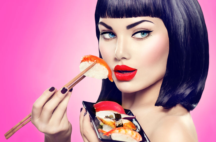 42872725 - beauty model girl eating nigiri sushi with chopsticks