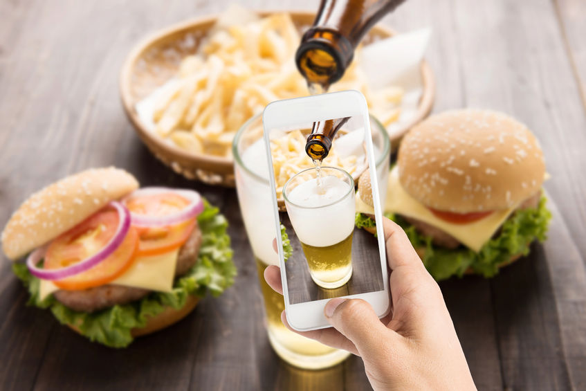 42935139 - using smartphones to take photos beer being poured into glass with gourmet hamburgers