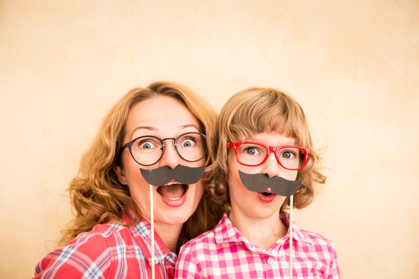 46594231 - mother and child with fake mustache. happy family playing in home