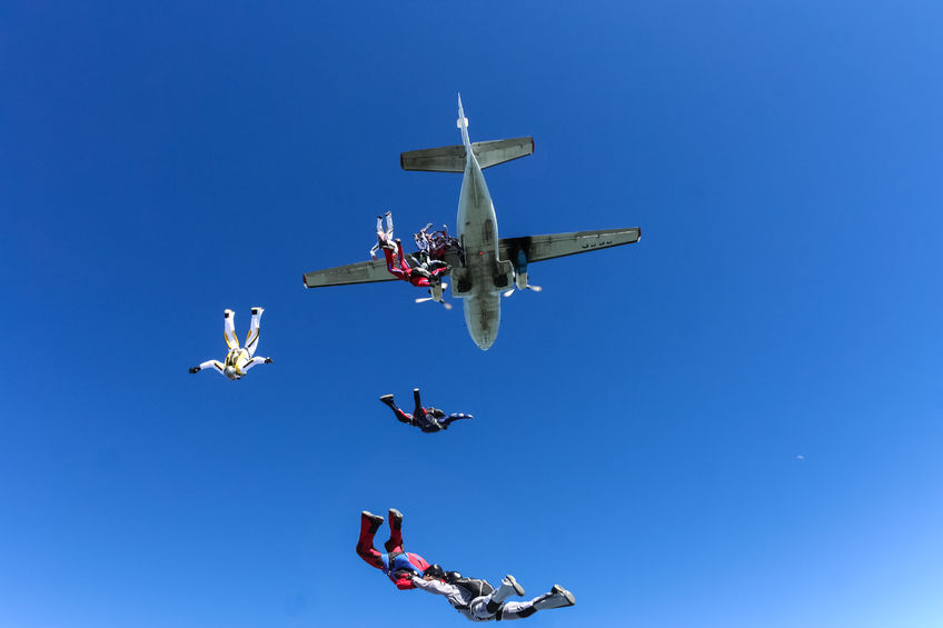 49348964 - a group of paratroopers jumping out of an airplane.