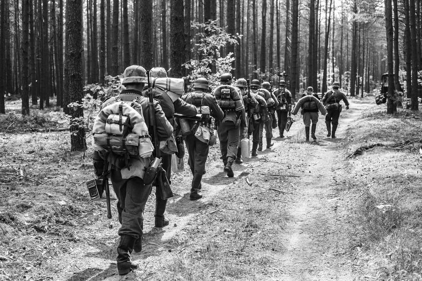 65313286 - unidentified re-enactors dressed as world war ii german soldiers walks on forest road. black and white photography