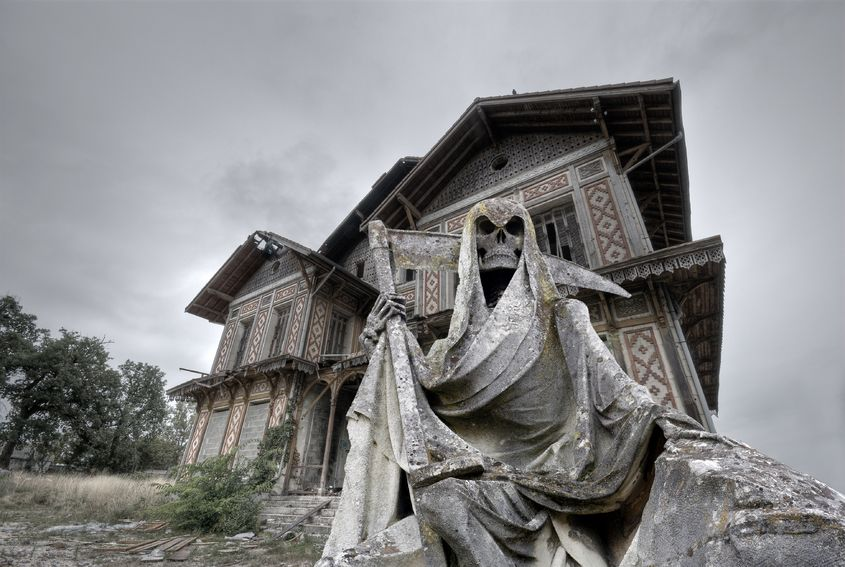 18658220 - haunted house abandoned and ruined manor with a gream reaper statue in foreground