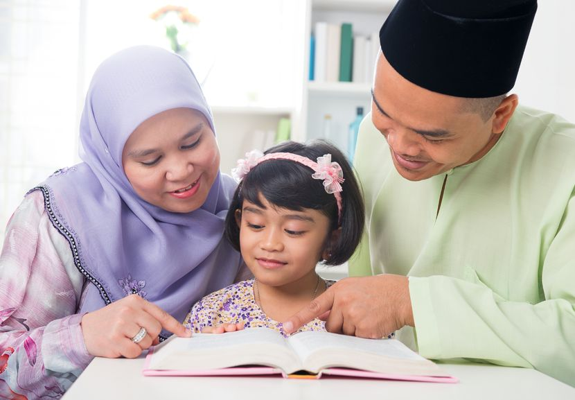 20434478 - malay muslim parents teaching child reading a book. southeast asian family at home.