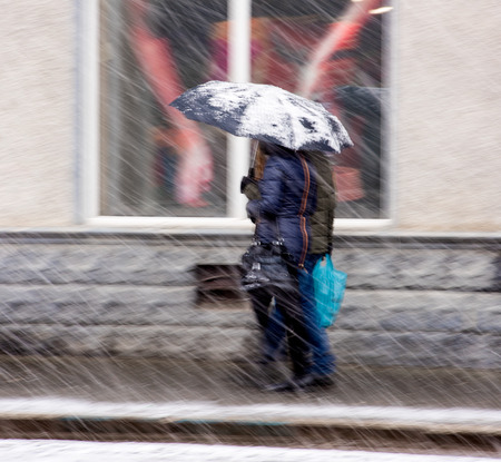 36868470 - people walking down the street in a snowy winter day in motion blur