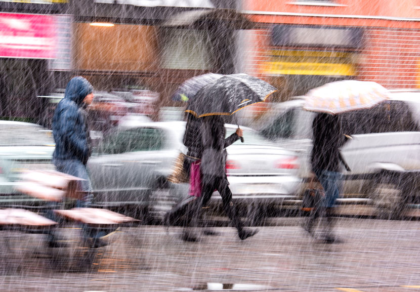 36868471 - people walking down the street in a snowy winter day in motion blur