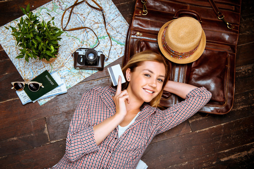 46697408 - top view photo of beautiful blonde girl lying on wooden floor. young woman smiling, holding credit card and looking at camera. passport, tickets, vintage camera, hat and map are on floor