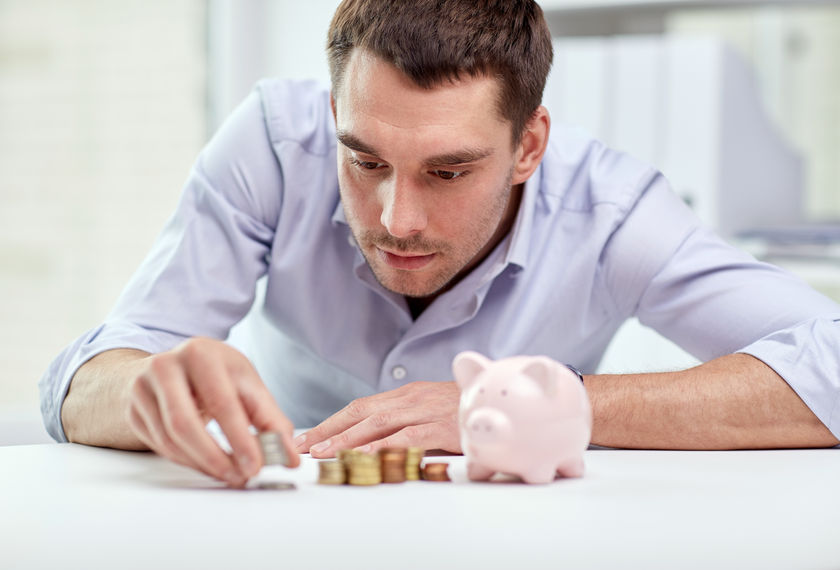 49042569 - business, people, finances and money saving concept - businessman with piggy bank and coins at office