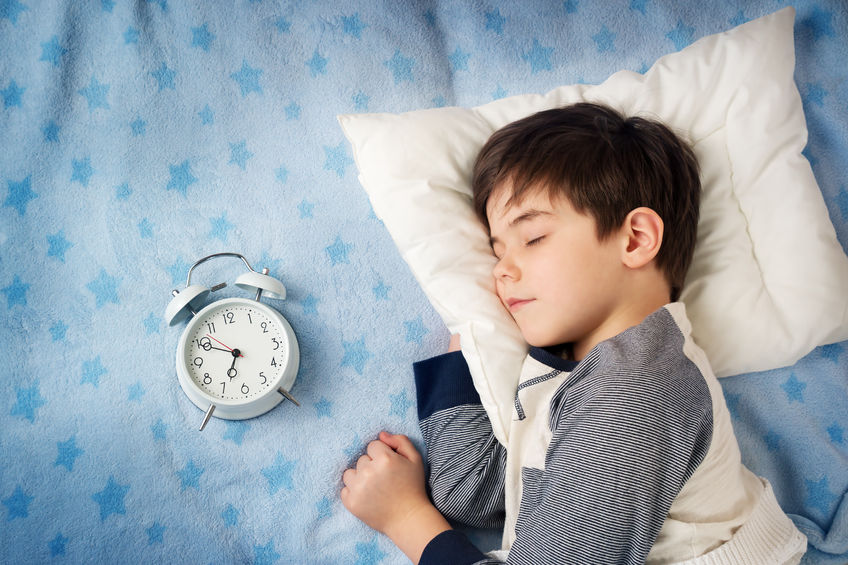 50431470 - six years old child sleeping in bed on pillow with alarm clock