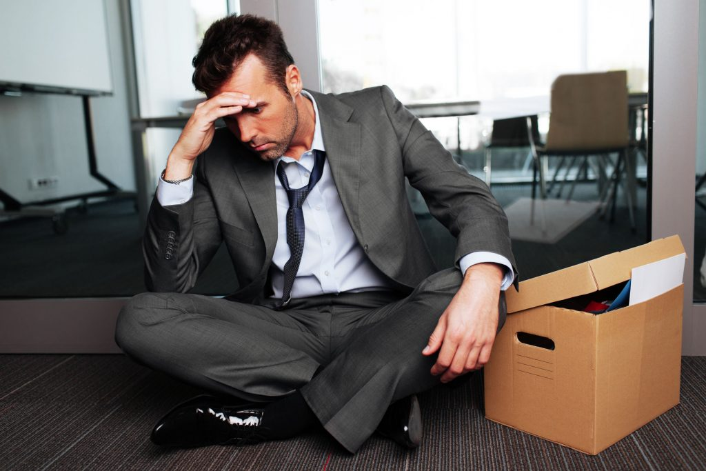 53957480 - sad fired businessman sitting outside meeting room after being dismissed