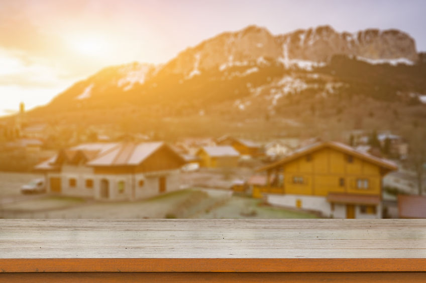 66428045 - empty brown wooden table top on blurred background of mountain ski resort with snow in winter,quaint village in the swiss alps during winter  - can be used for display or montage your products