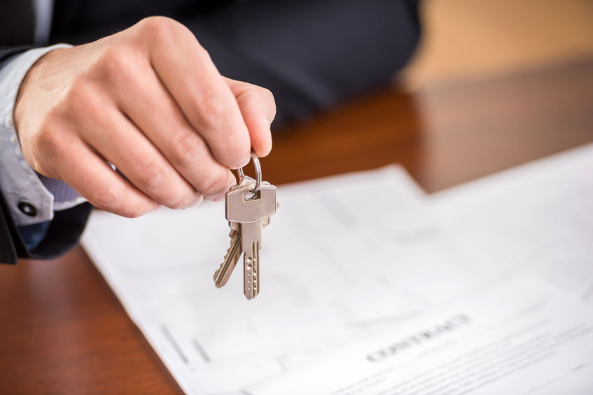 39395929 - close-up of hand of man is holding a key from a new apartment.
