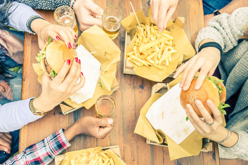 40113568 - group of friends toasting beer glasses and eating at fast food - happy people partying and eating in home garden - young active adults in a picnic area with burgers and drinks