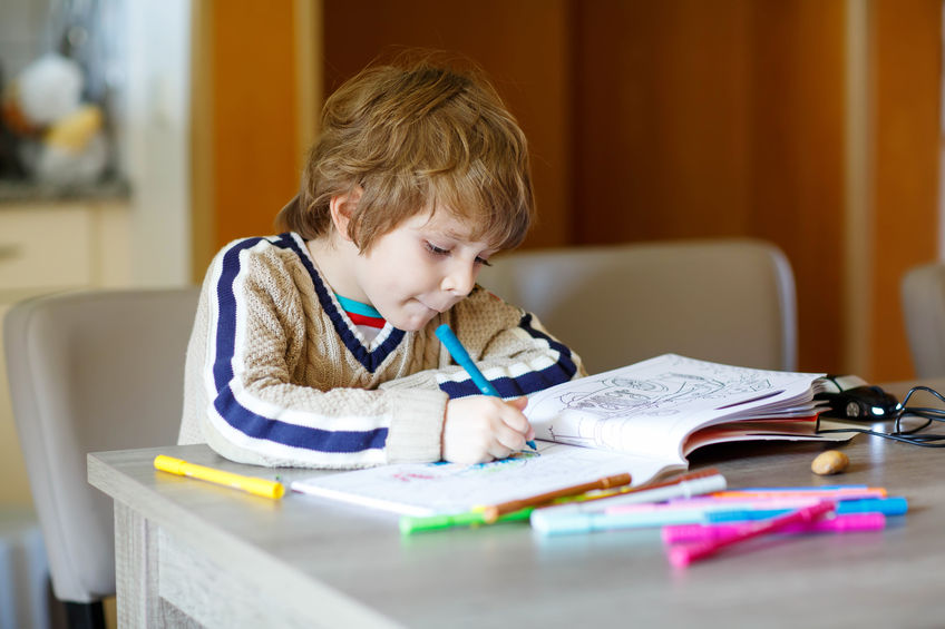 42706325 - portrait of cute happy preschool kid boy at home making homework. little child painting with colorful pencils, indoors.