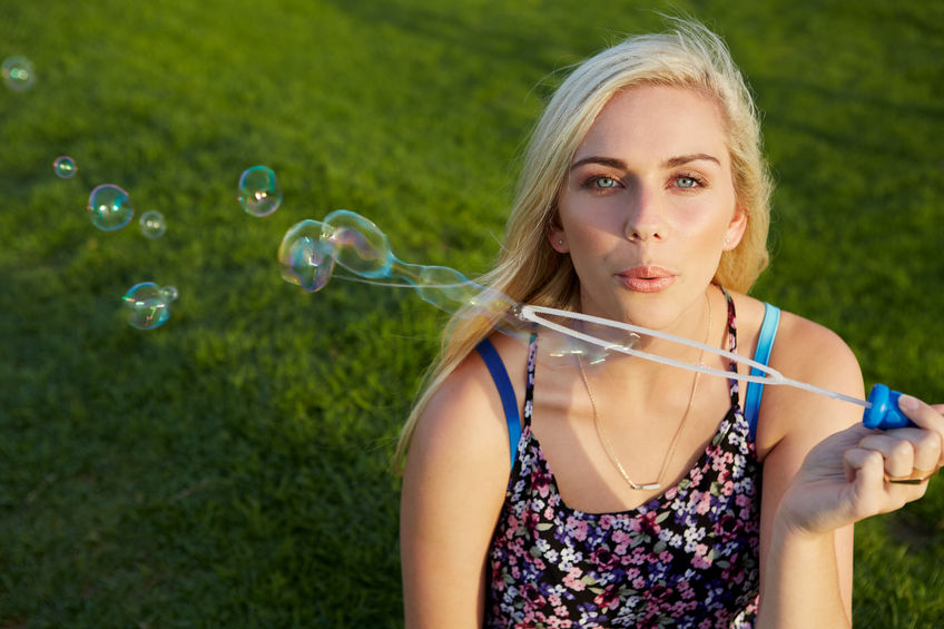 45974012 - attractive blonde woman blowing soap bubbles in park