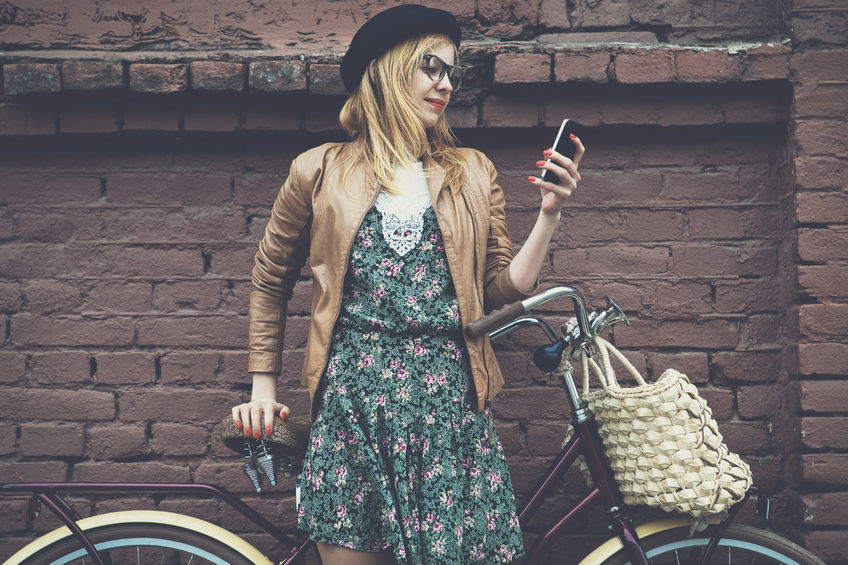 46656418 - city lifestyle stylish hipster girl with bike using a phone texting on smartphone app in a street