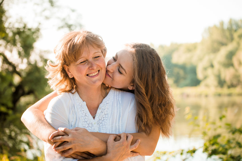 52579542 - mature mother hugging with her teen daughter outdoor in nature on sunny day