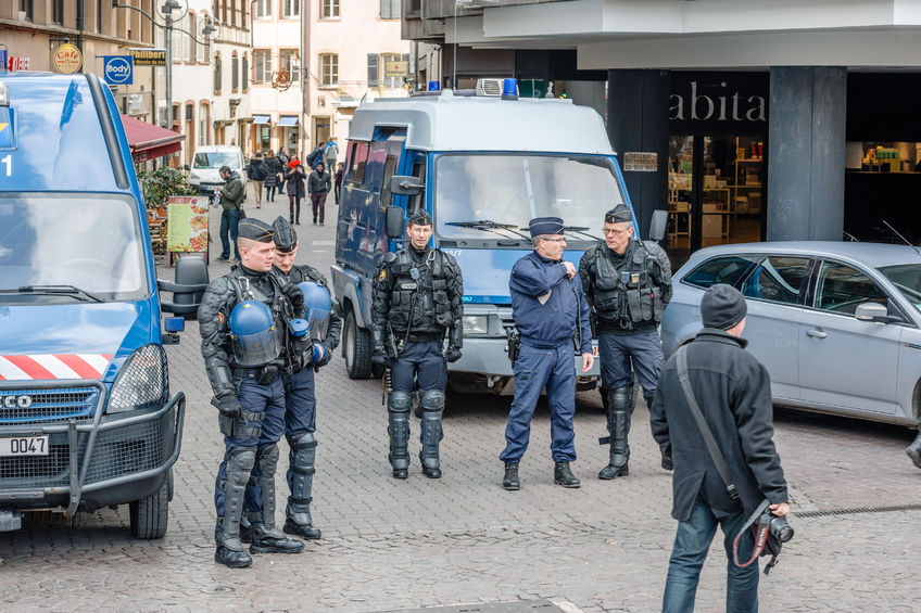 53419735 - strasbourg, france - 9 mar 2016: police officers surveilling street as thousands of people demonstrate as part of nationwide day of protest against proposed labor reforms by socialist government