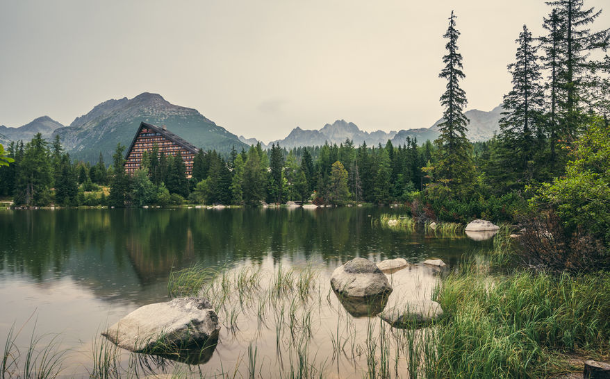61336744 - strbske pleso mountain lake in high tatras mountains, slovakia with rocks, trees and grass in foreground in the rain