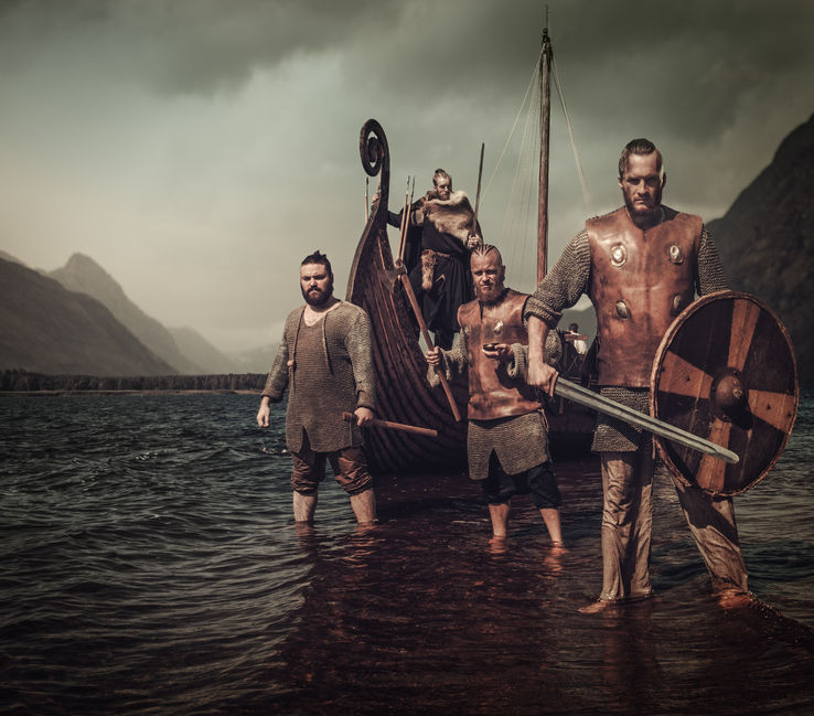 64798119 - armed, mad vikings warriors, standing on the seashore with drakkar on the background.