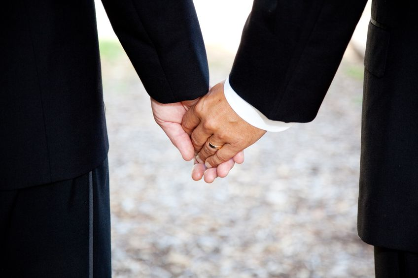 13626090 - closeup of a gay couple holding hands, wearing a wedding ring.  couple is a hispanic man and a caucasian man.