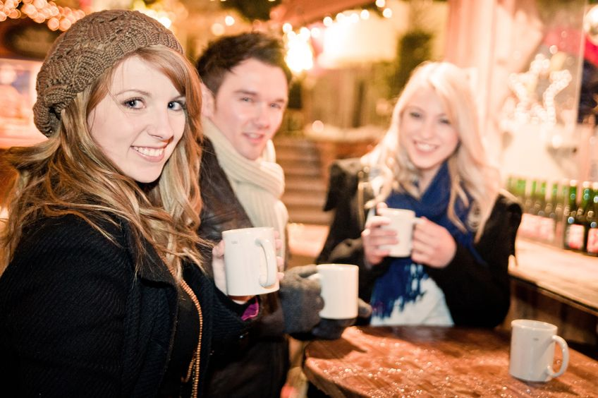 16253884 - three young people drinking punch at christmas market