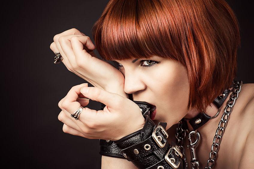 27346770 - beautiful fashionable woman gnaws leather handcuffs