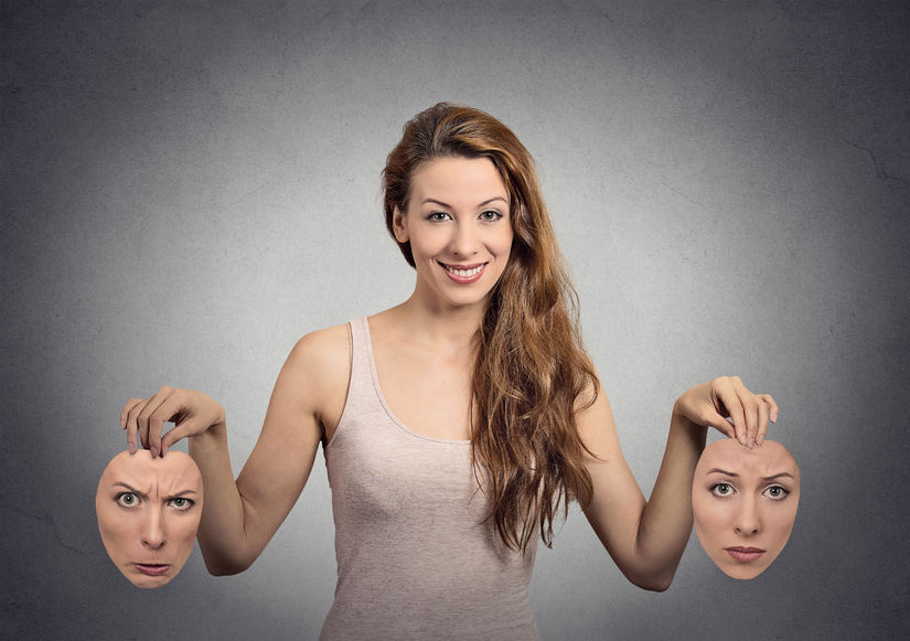 32554753 - portrait beautiful happy girl holds two masks isolated grey wall background. human face expressions, emotions, feelings, bipolar state of mind concept