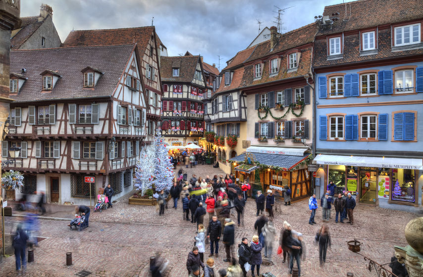 33361201 - colmar, france- decmebr 06,2013: people walking in a town square between traditional half-timber houses and specific christmas decoration in colmar, alsace, france. hdr image with selective motion blur on some of the people. colmar is considered to be the