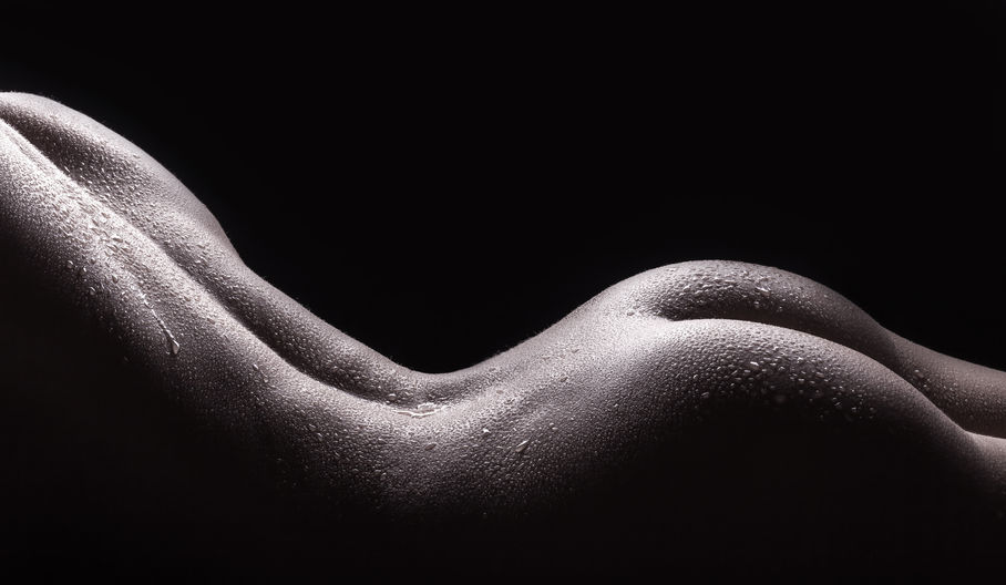36734424 - beautiful buttocks of a nude young woman with wet body, closeup on dark background