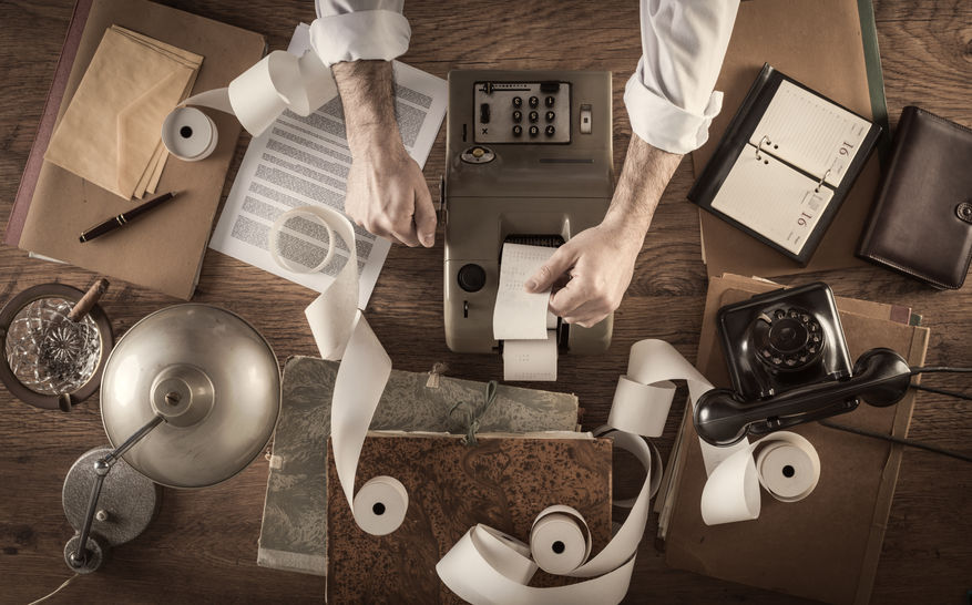 43569268 - messy vintage accountant's desktop with adding machine and paper rolls, he is working with the calculator