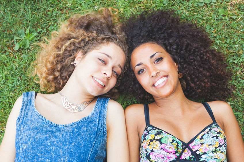 44119094 - a multiracial couple of women lying on the grass. they are two young women resting at park. one is caucasian blonde and the other is black brunette, both have curly hair. they are smiling and wearing summer clothes.