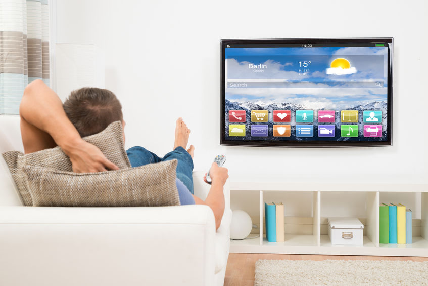 44589454 - young man lying on sofa using remote control in front of television