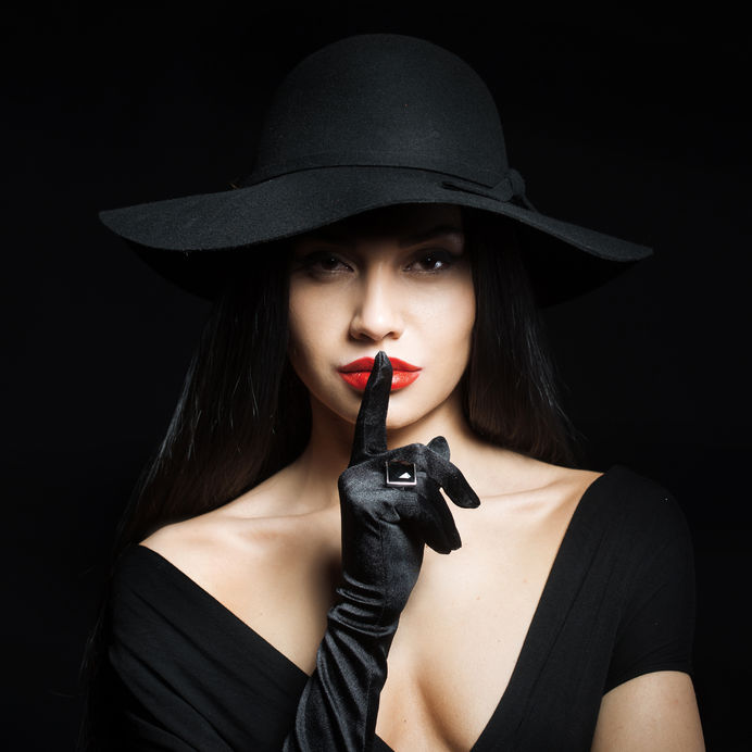 44816380 - woman in big black hat making a silence gesture, studio portrait, dark background