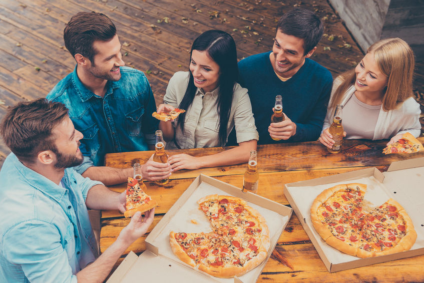 45174916 - enjoying time together. top view of five happy young people holding bottles with beer and eating pizza while standing outdoors