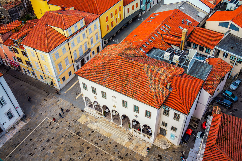 60003785 - central square of coastal town koper in slovenia seen from above. historical buildings with red roofs, cafes, shops and restaurants