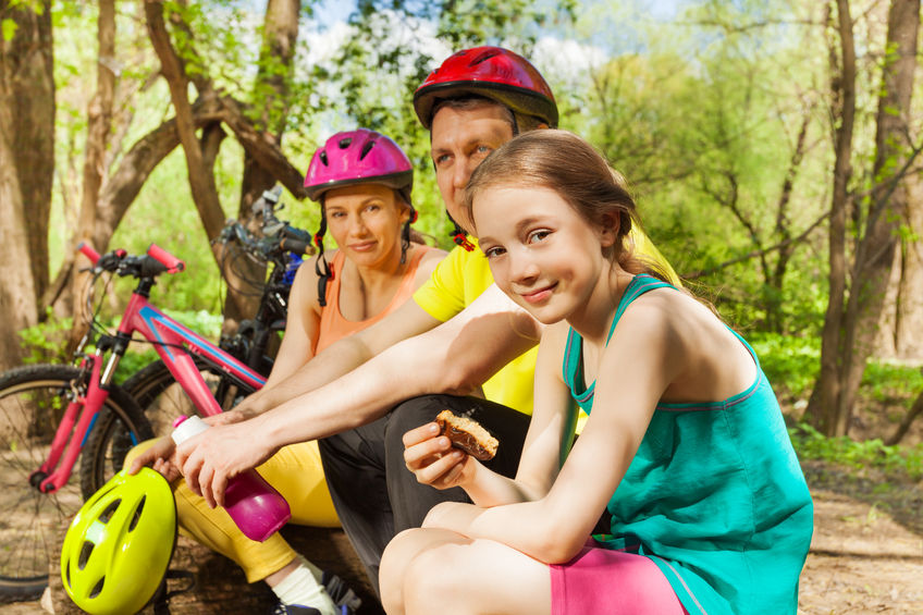 60345750 - active family, father, mother and young girl, refreshing after cycling their mountain bikes in the sunny spring wood
