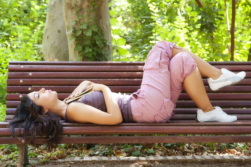 8690278 - beautiful woman dreaming after reading in a park bench.