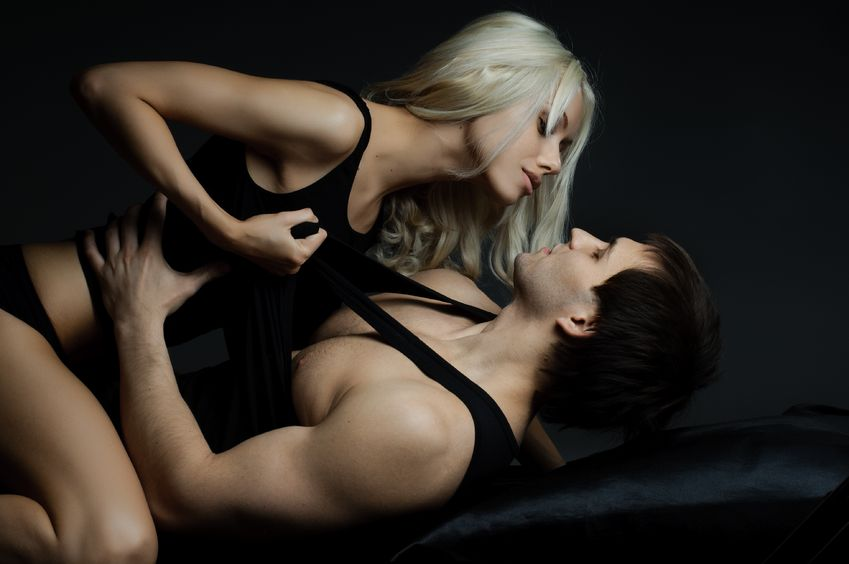 13589985 - muscular handsome sexy guy with pretty woman, on dark background, glamour  light