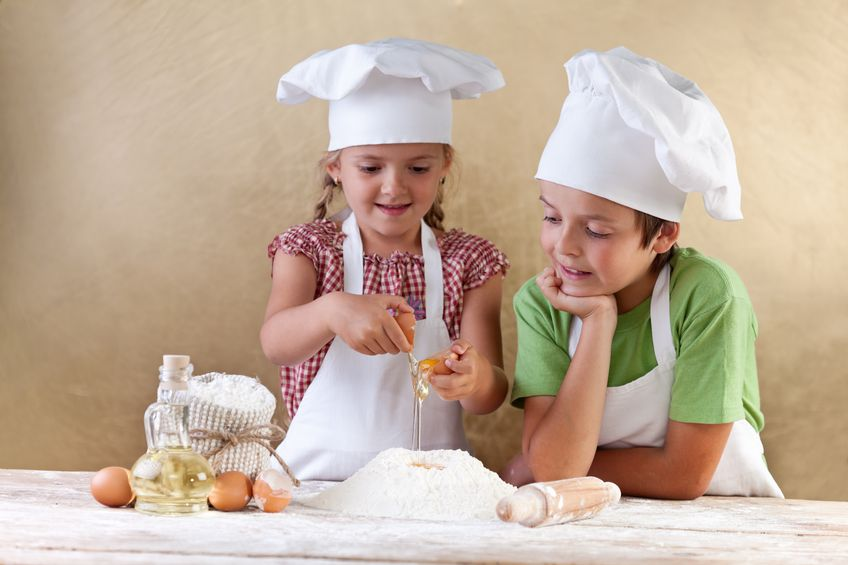15891808 - kids with chef hats preparing tha cake dough - mixing ingredients