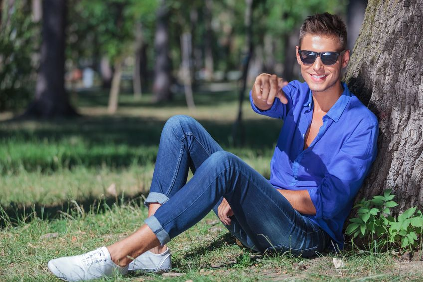 18600636 - young casual man sitting on the ground next to a tree and pointing at the camera while smiling
